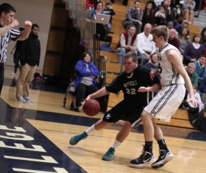 Matt Langadas (19 points) tries the baseline against Hans Miersma
