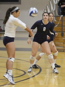Maggie Risma digs as Carleigh Petersen looks on