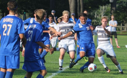 Josh Cochran (10), Charlie Mader (18), and Tyler Modzeleski (17) converge on the ball